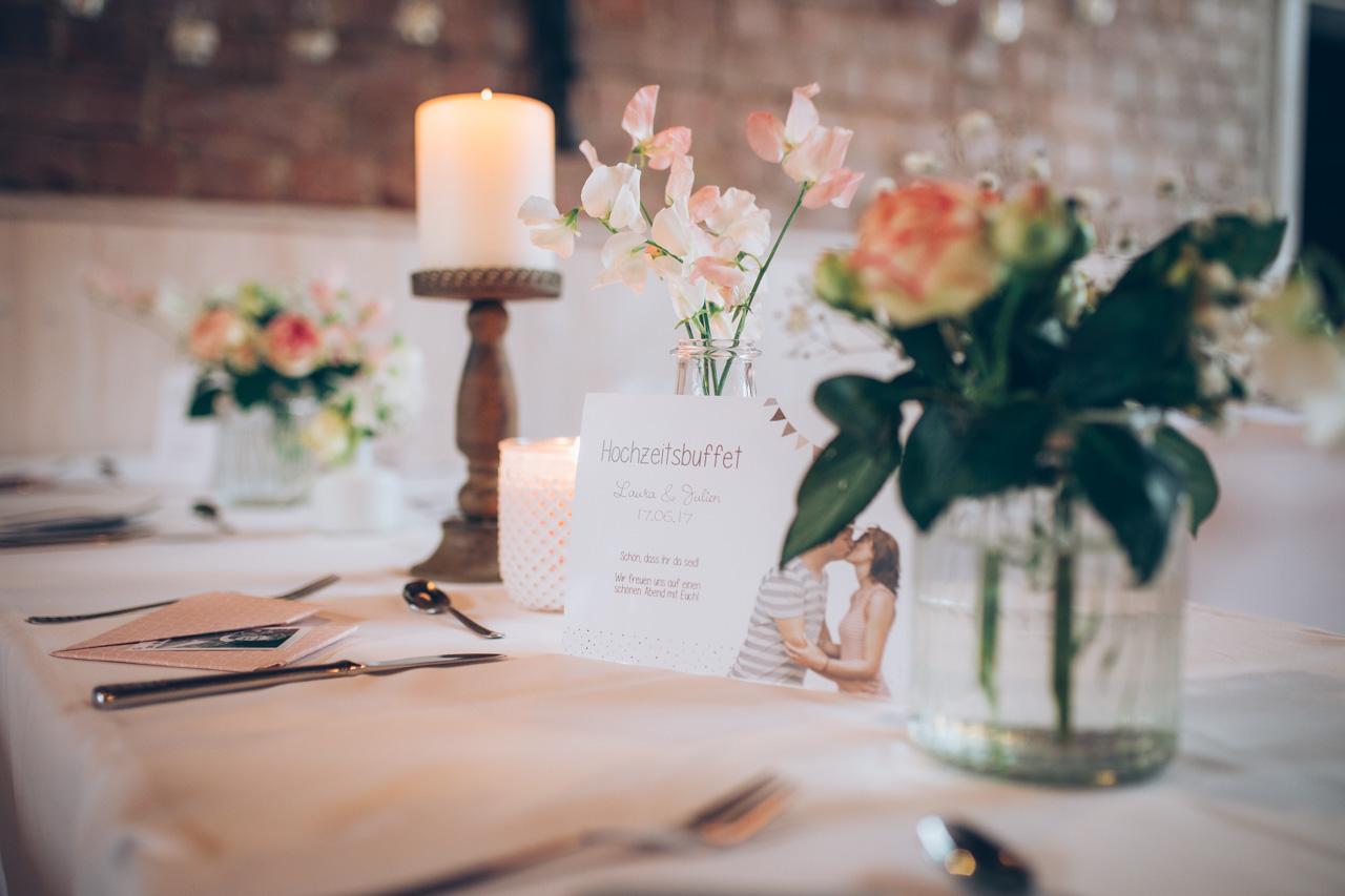 Hochzeitstisch mit Kerzen, Blumen und Karte